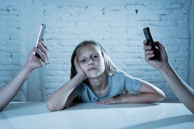 mother and father using mobile phones neglecting little sad ignored daughter bored and lonely feeling abandoned and disappointed with  parents.  mobile cell smart phone addiction bad behavior concept