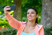 good looking slim adult sexy fit sporty latin woman in sportswear in a modern city park morning after doing exercise make selfie on her phone in fitness and