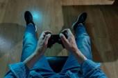 Sucht- und Abhängigkeitskonzept. Nahaufnahme auf den Händen eines jungen Mannes mit einem Joystick, der Videospiele spielt. Mann süchtig nach Konsolen-Spielkonzept.