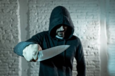 close up of hand holding a knife of dangerous hooded man standing in the dark.  London knife crime concept.