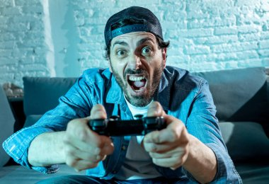 Young excited latin man at home sitting in living room on  sofa and  playing video games using remote control joystick with freak intense face expression having fun in gaming addiction concept stock vector