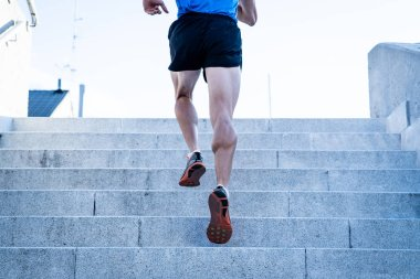 Man runner running on stairs in urban city sport training young male jogger athlete training and doing workout outdoors in city. Fitness and exercising outdoors urban environment concept.