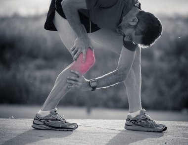 Closeup black and white of sport guy runner injuring his knee after a run injury highlighted in red to show where the pain is in sports fitness injury concept.