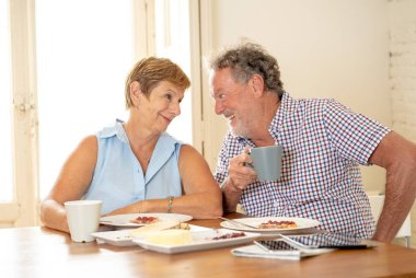 Attractive mature retired couple having breakfast together at home