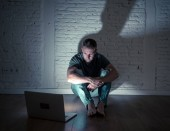 Fotografie Men suffering Internet cyber bullying
