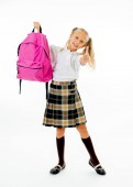 Photo Pretty cute blonde hair girl with a pink schoolbag looking at camera showing thumb up gesture happy to go to school isolated on white background in back to school and children education concept