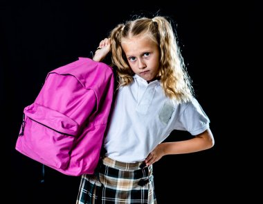 unhappy school girl holding a big schoolbag full of books and homework on black background. learning difficulties homework and education concept.