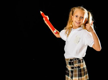Adorable blonde schoolgirl in uniform writing on the blackboard with big red pencil and showing thumb up