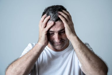 Portrait of an attractive man sad an depressed suffering depression feeling sorrow and pain in human emotions facial expressions and depression concept isolated on grey blue background