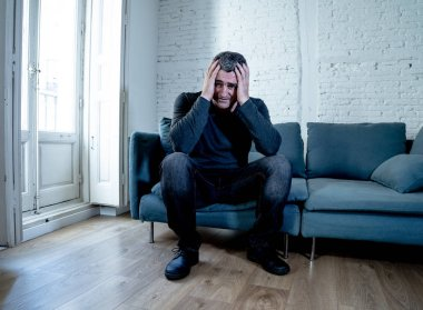 Attractive man feeling desperate sad looking worried depressed thoughtful and lonely suffering depression on couch at home in middle age crisis mental health personal problems and life style concept.
