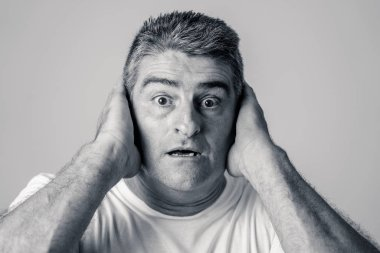 Portrait of a 40s 50s man in shock with a scared expression on his face making frightened gestures in human emotions feelings and facial expression concept isolated on grey background.