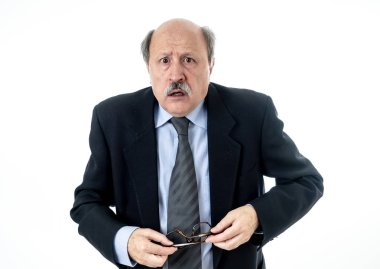 Portrait of a 60s senior man in shock with a scared expression on his face making frightened gestures in human emotions feelings facial expression and bullying at work concept isolated on grey background.