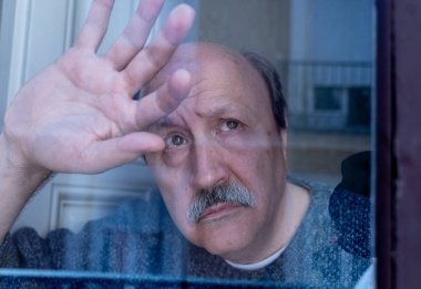 Old senior man looking throughout the window feeling confused and depressed alone at home in Aging Retirement Widower Dementia and Alzheimer concept.