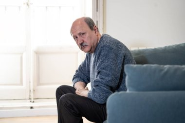 Senior old man feeling desperate sad looking worried depressed thoughtful and lonely on couch at home in Aging Mental health Personal problems and Life style concept.