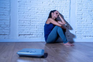Young anorexic teenager woman sitting alone on ground looking at the scale worried and depressed in dieting and eating disorder concept