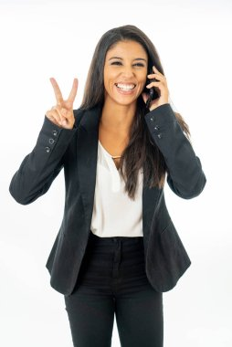 Full length portrait of Attractive latin corporate latin woman talking on smart phone and making victory sign in Creative success and happiness at work concept isolated on white background