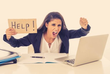 Young attractive businesswoman working on computer laptop suffering stress at office going crazy holding a help sign