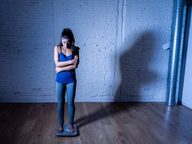 Young fit and slim woman checking body weight on scale finding herself fat and feeling depressed and desperate in failing diet eating disorder and dieting concept.