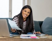 Attractive smiling latin woman paying bills accounting costs charges taxes and mortgage at home using calculator and laptop looking pleased and happy in e-banking and home finance concept.