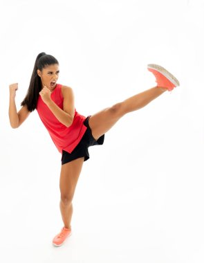 Young and furious latin woman in fight and kick boxing training workout throwing aggressive kick attack isolated on white background in fitness sport gym exercise and personal defense concept.