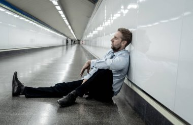 Desperate sad young businessman suffering emotional pain grief and deep depression sitting alone in tunnel subway in Stress life style Work problems failure Unemployment Mental health and Depression.