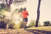 Happy běžec v sportovní běh školení pro maratón venku v parku při západu slunce na krásné letní den v Sports zdravého životního stylu a Jogging Cross Country školení cvičení venku koncepce.