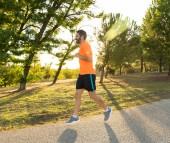 Happy běžec v sportovní běh školení pro maratón venku v parku při západu slunce na krásné letní den v Sports zdravého životního stylu a Jogging Cross Country školení cvičení venku koncepce