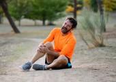 Mladá vešel muž, který držel koleno s rukama v bolesti poté, co utrpěl svalové zranění zlomenina nohy bolest výron nebo křeče během tréninku se systémem v parku venku v sportovního tréninku běh zranění.
