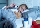 Süße krank niedliche Mädchen Übelkeit im Bett liegend mit Medikamenten Thermometer Warmwasser Tasche leiden unter Kälte und Winter-Grippe-Virus Niesen laufende Nase und Haar in der Suppe Krankheitssymptome in der Child Health Care