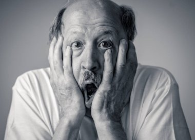 Close up portrait of a scared frightened old man in expression of fear in human emotions and facial expressions isolated in neutral background.