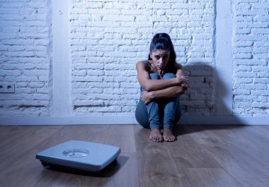 Young anorexic bulimic teenager woman sitting alone on ground looking at the scale worried and depressed in failing dieting and eating nutrition disorder concept.