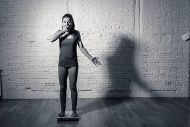 Young fit and slim woman checking body weight on scale finding herself fat and feeling depressed and desperate with big edgy shadow light in eating disorder and dieting concept.