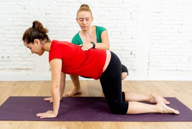 Attractive yoga therapist teacher helping beginner young woman with yoga cow pose in studio home as Private yoga lessons Wellness Fitness and emotional physical and mental Well being concept.
