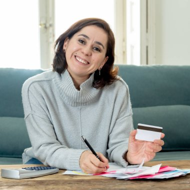 Young attractive latin business woman looking happy and satisfied with credit debit card advantages and use and accounting costs, charges, taxes and mortgage with calculator on sofa at home .