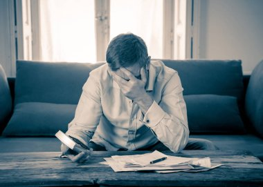 Worried and desperate entrepreneur young man calculating bills tax expenses and counting business or home finances sitting on couch at home in paying off debts banking and financial problems concept.
