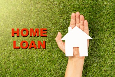 Conceptual picture of woman hand holding white house and text Home Loan on green grass field top view in Property investment Real estate Saving and buying a house mortgage and banking concept.