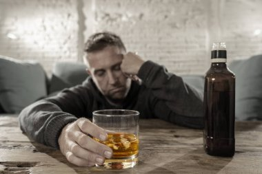 Drunk young man drinking alcohol at home felling lonely depressed and sick holding a glass of whiskey image in white and black and drink in color in Alcohol Addiction Social drug and Abuse concept.