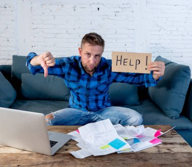 Worried and stressed man calculating bills Tax expenses and counting home finances sitting on couch in living room at home in paying off debts and domestic bills and financial problems concept.