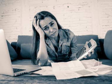 Portrait of young single mother business woman feeling stressed accounting finances with laptop and calculator in living room in Paying off debts and Domestic bills and financial problems concept.
