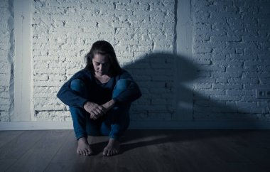 Young devastated depressed woman crying feeling hurt suffering depression in Sadness Emotional pain and Human Expression and Loneliness and heartbroken concept with copy space and dramatic dark light.