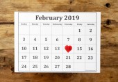 Calendar page with red heart on February 14 th of Saint Valentines day on vintage wooden rustic background in Romantic love Celebration and Valentines Day greetings card design concept. Top view