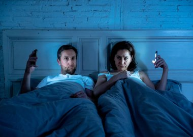 Couple affected by technology addiction ignoring at each other in apathy and anger lying in bed using their smart phones late at night in darkness in relationship issues and internet mobile addiction.