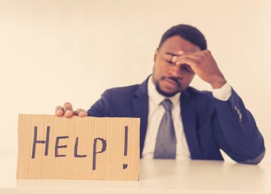 Young attractive and frustrated african american businessman holding message asking for help feeling sad and overworked in corporate job problem, business crisis and unemployment Depression concept.