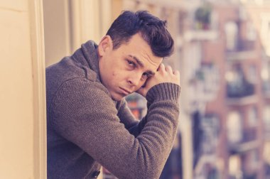 Sad unhappy depressed young man crying and suicidal feeling desperate, isolated and worthless staring down the street on home balcony In People Depression and Mental Health concept. Urban background.