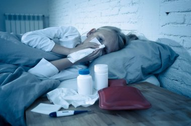 Sweet sick cute girl feeling sick lying in bed with medicines thermometer hot water bag suffering from Cold and Winter Flu Virus Sneezing Running Nose and Gripe Disease Symptoms in Child Health Care.