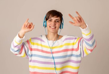 Portrait of gorgeous and happy brunette woman in colorful striped jumper listening music in headphones singing and dancing on neutral background. In positive emotions, youth and happiness concept.