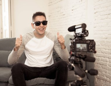 Happy trendy caucasian male on his twenties filming video blog on camera with tripod for online followers at home. In social media, Influencer, new technology, communication and internet concept.