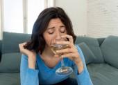 Portrét depresivní ženy, která pije sklenici vína sama doma. Pocit úzkosti, beznadějný a frustrovaný, snaže se cítit lepší pití. Nezdravý chování, deprese a koncepce alkoholu.