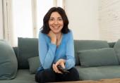 Életmód portréja vidám fiatal nő ül a kanapén tévénézés gazdaság távirányítóval