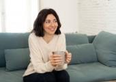 Životní styl portrét mladé, uvolněné ženy konzumní horkou kávu nebo čokoládový pocit šťastný a útulný doma se šťastně usmívající na gauči. Ve volném čase, v klidném životě, pojetí stylu štěstí.